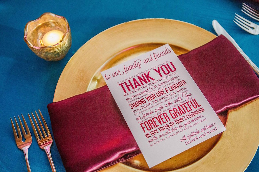 Gold and Purple Wedding Table Setting with Gold Charger and Magenta Red Napkin and Thank You Stationery Menu Card on Teal Linens | Arabic Theme Wedding Decor Ideas | St. Petersburg Wedding Planner Exquisite Events