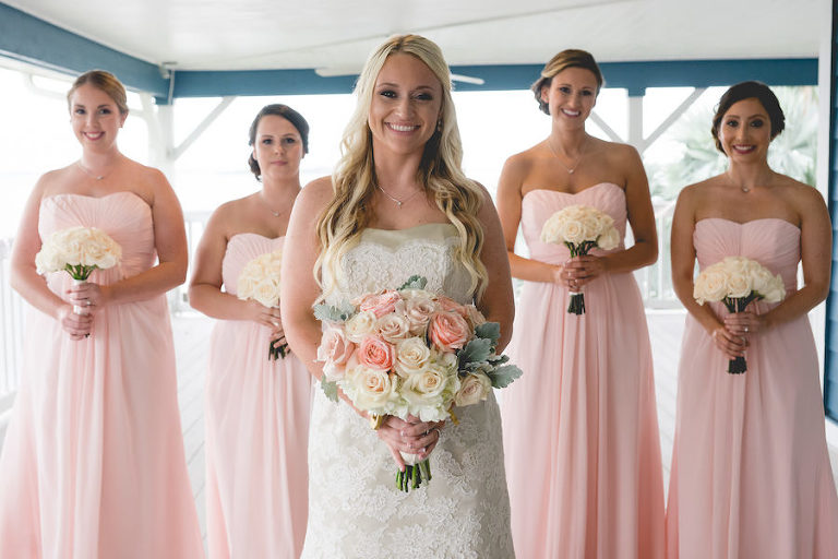 Outdoor Bridal Wedding Portrait of Bride and Bridesmaids in Lace, Ivory Modern Trousseau Wedding Dress and Pink Strapless Sweetheart Bridesmaids Dresses with Pink and Ivory Floral Bouquets of Roses