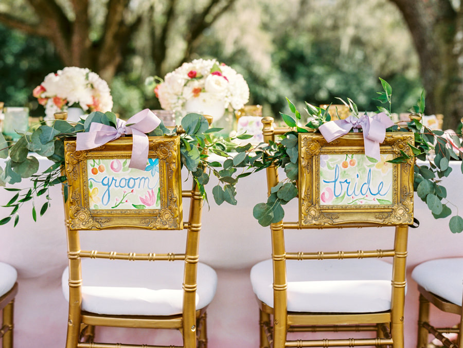 Outdoor Tampa Wedding Reception Seating with Watercolor Bride and Groom Chair Signs with Greenery with Gold Chiavari Chairs | Tampa Wedding Rental Chairs by Signature Event Rentals