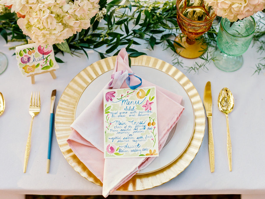 Wedding Reception Place Setting with Gold Charger and Gold Silverware with Watercolor Menu Card with PersonalIzed Cookie Favor with Name Card and Hydrangea Floral Decor | Tampa Wedding Rentals by Ever After Vintage Rentals