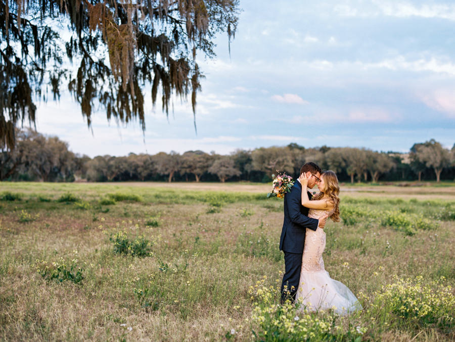 Bride and Groom Outdoor Tampa Wedding Portrait in Meadow of Greenery