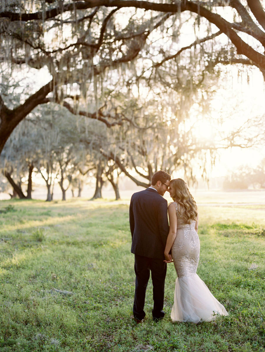 Bride and Groom Outdoor Tampa Wedding Portrait in Meadow of Greenery with Oak Trees