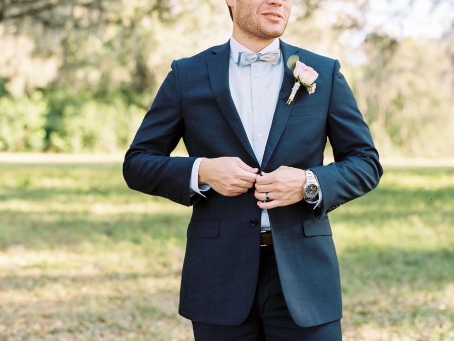 Wedding Portrait of Groom in Navy Suit with Bowtie and Pink Rose Boutonniere