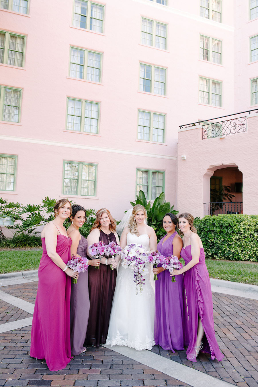 Outdoor St Pete Bridal Party Wedding Portrait | Purple and Fuchsia Mismatched Dessy Collection Bridesmaid Dresses with Ivory Sweetheart Narin Moda Wedding Dress and Pink, White and Purple Wedding Bouquet | Wedding Hair and Makeup Artist Michele Renee The Studio