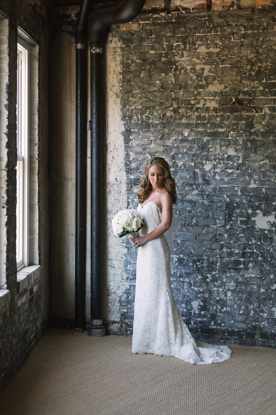 Bridal Wedding Portrait in Ivory, Lace Strapless Dress, Lace Veil, and White Floral Wedding Bouquet of Flowers with Industrial Brick Wall Backdrop