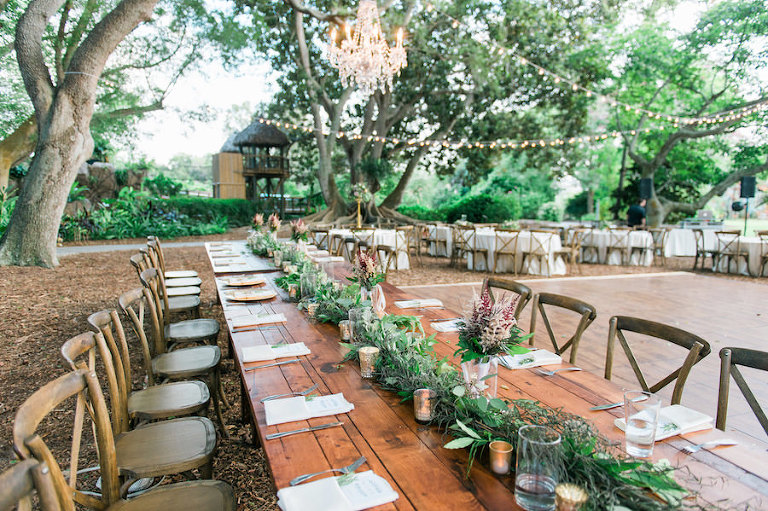 Rustic Wedding Reception with Wooden Feasting Farm Tables and Crystal Chandelier with Twinkle Lights at Sarasota Wedding Reception Venue Marie Shelby Botanical Gardens | Sarasota Wedding Florist Andrea Layne Floral Designs | Rentals by A Chair Affair
