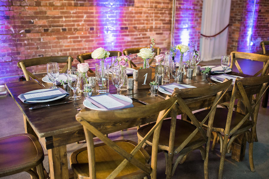 Rustic Garden Wedding Reception Table Decor with Farmhouse Table, Wooden Chairs, and Ivory and Purple Floral Centerpieces   Tampa Wedding Chair Rentals A Chair Affair   Tampa Wedding Venue CL Space