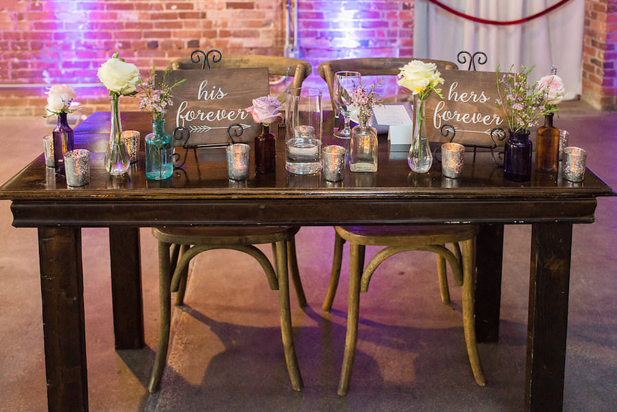 Rustic Garden Wedding Reception Sweetheart Table Decor with Farmhouse Table, Wooden Chairs, and Ivory and Purple Floral Centerpieces   Tampa Wedding Chair Rentals A Chair Affair   Tampa Wedding Venue CL Space