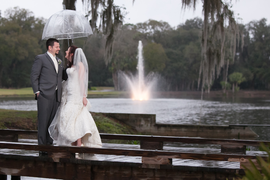 Outdoor, Bride and Groom Wedding Portrait on Dock with Fountain and Umbrella During Rain in Ivory, Lace Wedding Gown   Wedding Photographer Carrie Wildes Photography   Tampa Wedding Venue Tampa Palms Golf and Country Club