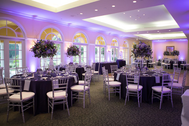 Purple Wedding Reception Table Decor | Silver Chiavari Chairs, Purple and Ivory Tall Table Floral Centerpieces, and Purple Uplighting | Tampa Wedding Venue Tampa Palms Golf and Country Club