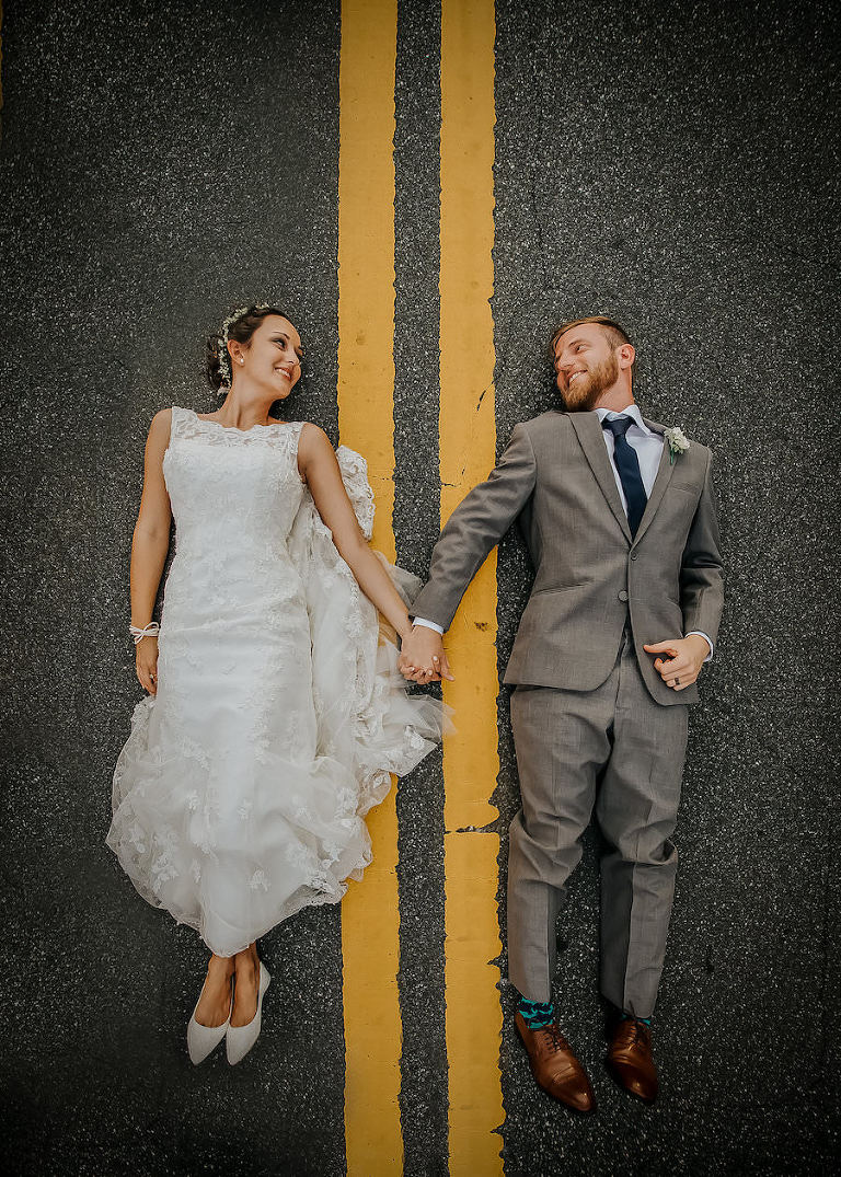 Outdoor, Bride and Groom Wedding Portrait Laying in Road in Ivory, Lace Wedding Dress and Grey Groom's Suit | Lakeland Wedding Photographer Rad Red Creative
