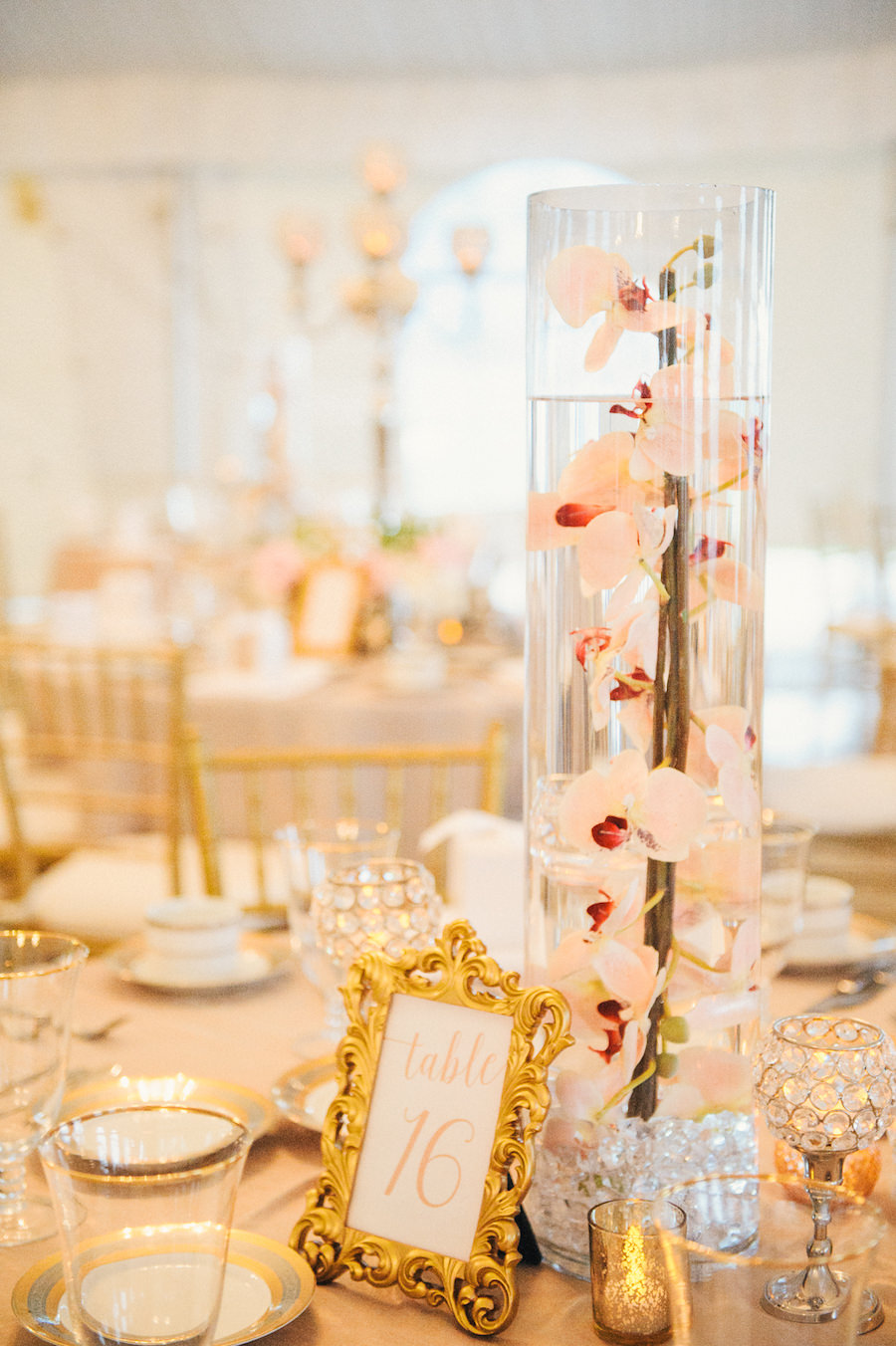 Blush and Gold Wedding Reception with Tall Submerged Orchids in Glass Vase Wedding Centerpieces on Blush Linens with Gold China and Chiavari Chairs   Sarasota Wedding Planner NK Productions