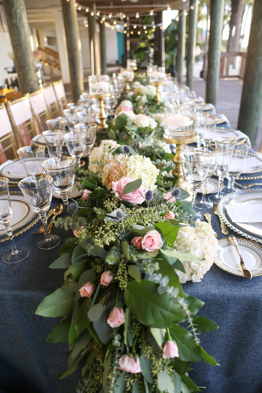 Cascading Blush Roses with Greenery Wedding Table Garland Centerpiece by Iza's Flowers   Ivory China with Art Deco-Inspired Gold Detail from A Chair Affair on Glass Beaded Charger from Signature Event Rentals and Slate Blue Burlap Linens by Over The Top Rental Linens
