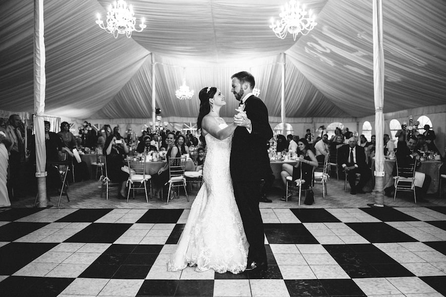 Bride and Groom First Dance on Wedding Day Portrait in Tented Reception with Checkered Dance Floor   Sarasota Wedding Planner NK Productions