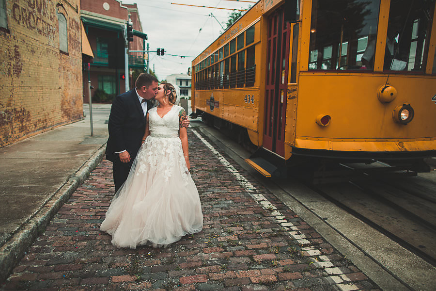 Historic Tampa Bride and Groom Wedding Portrait in Black Tuxedo and Allure Cap Sleeve Tulle and Lace Wedding Gown | Ybor City Trolley Car