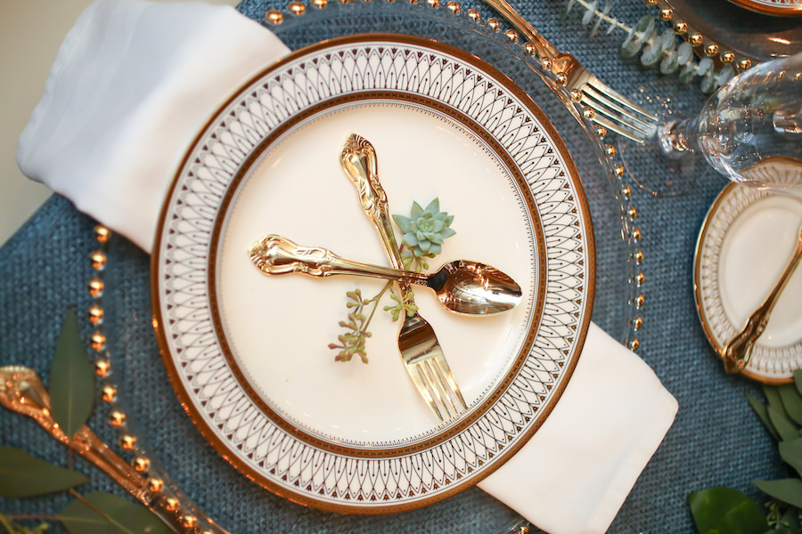 Elegant Boho Beach Wedding Reception Table Décor with Navy Burlap Linens and Gold-Trimmed, Ivory China with Gold Silverware   Linens by Over The Top Rental Linens   China/Glassware by A Chair Affair   Glass Beaded Charger by Signature Event Rentals