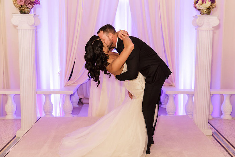 Wedding Portrait First Kiss with Purple Uplights with White Draping at Wedding Reception by Tampa Bay DJ Graingertainment