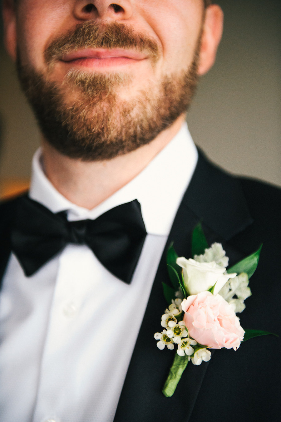 Groom in Black Tuxedo with Black Bowtie wearing Blush Pink and Ivory Wedding Boutonniere