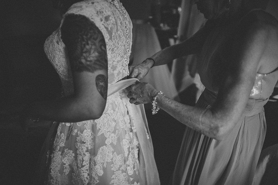 Bridesmaids Helping Put Wedding Dress on Bride