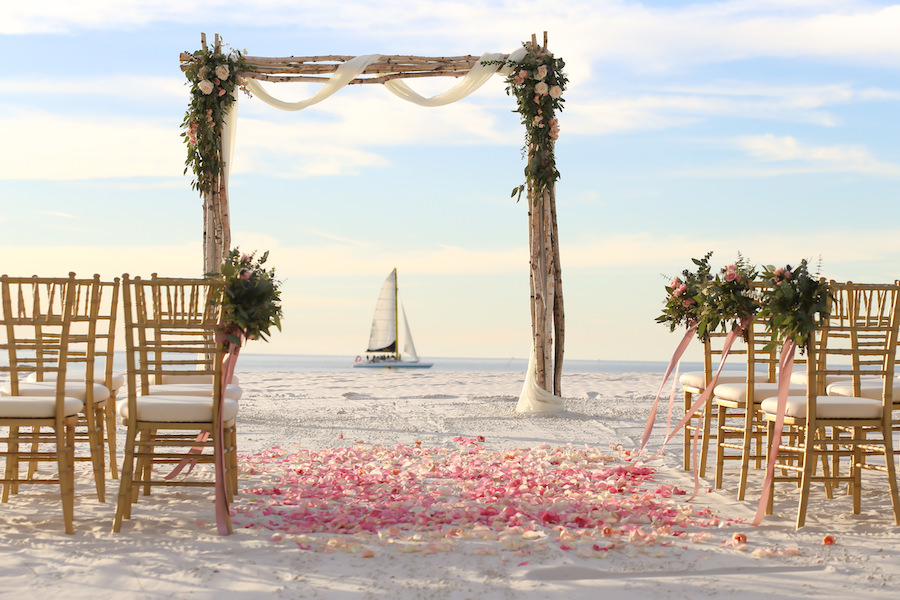 Florida Beach Oceanfront Wedding Ceremony Decor at Wedding Venue Hilton Clearwater Beach | Floral Chair Décor and Driftwood, Tulle and Rose Wedding Arch by Iza's Flowers | Gold Chiavari Chairs by Signature Event Rentals