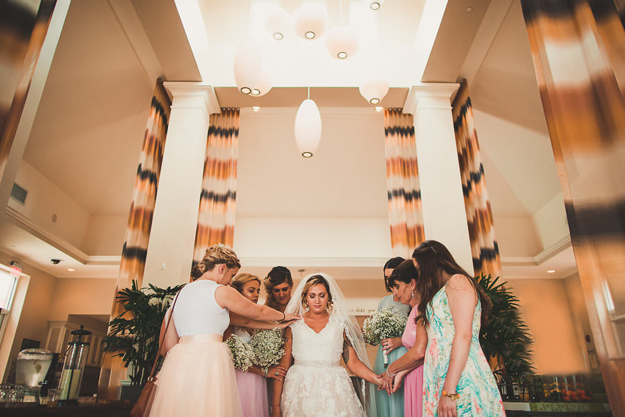Bridal Party Praying With Bride Before Wedding Reception