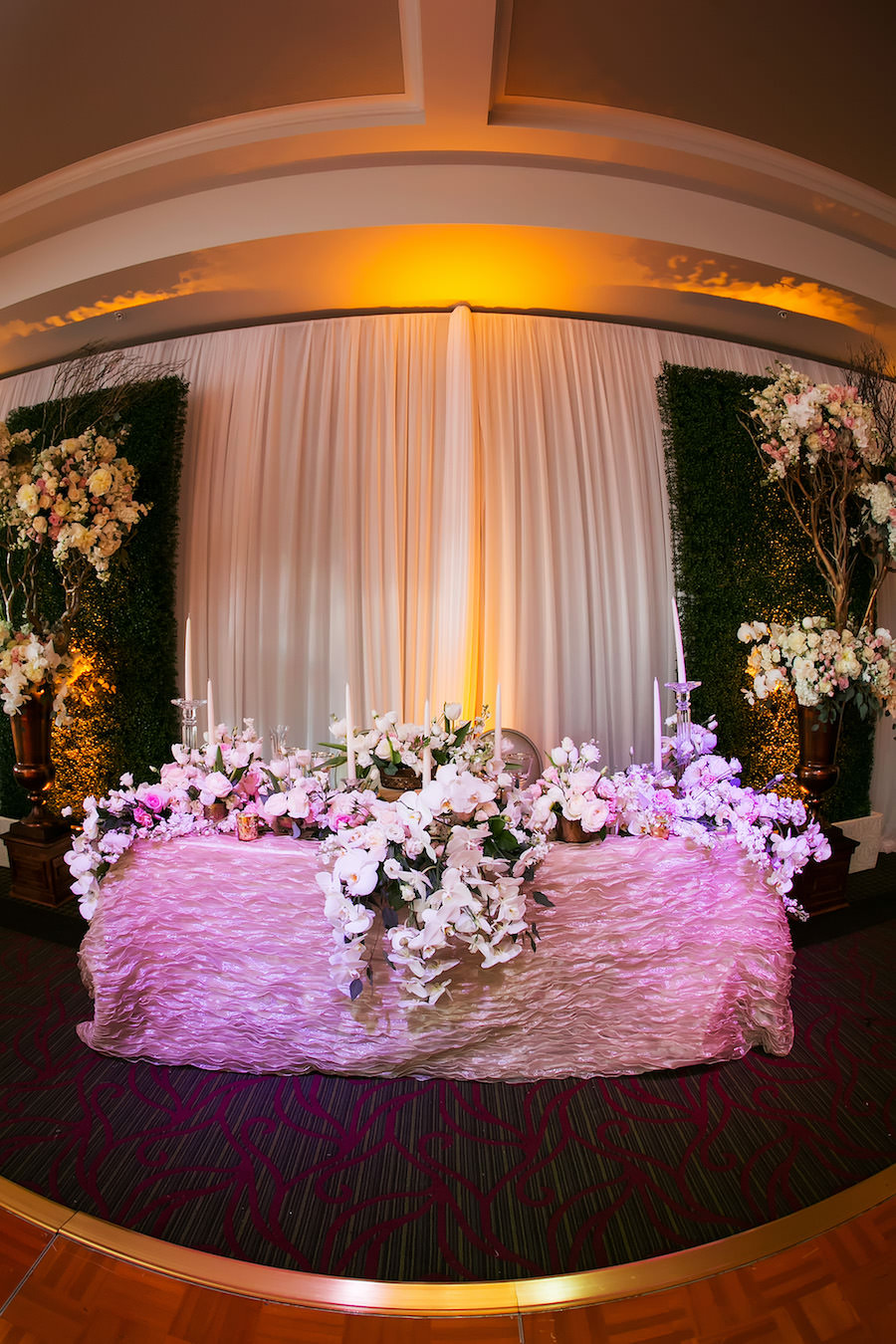 Orchid Flower Wedding Head Table Centerpieces with Candles on Champagne Specialty Linens at Downtown St. Petersburg Wedding Venue The Birchwood   Linen Rentals by Over The Top Linens   Photography by Limelight Photography