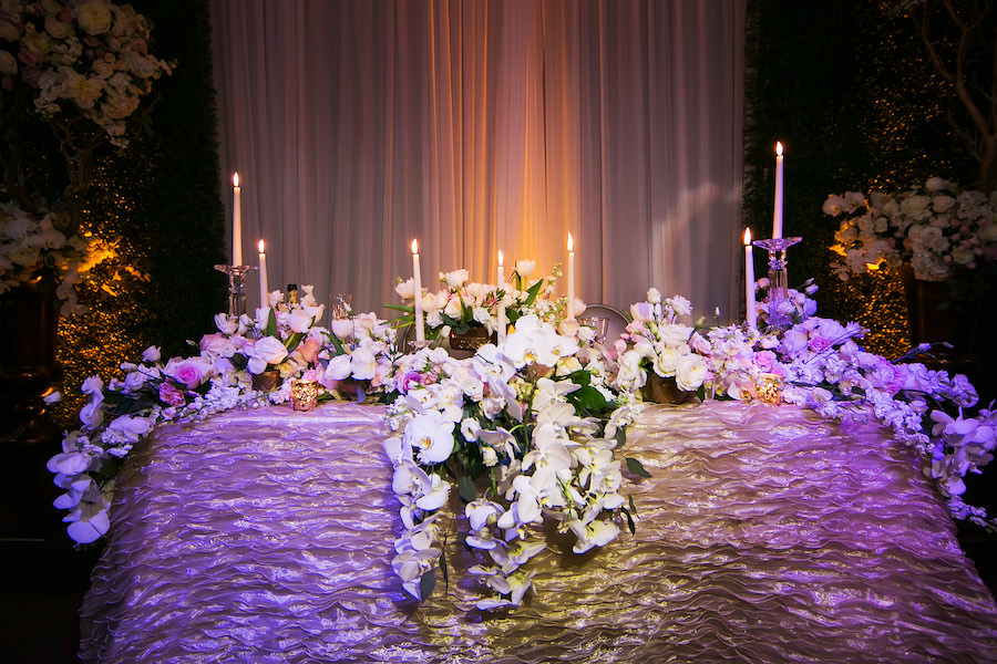 Cascading Orchid Wedding Head Table Centerpieces with Candles on Champagne Specialty Linens   St. Petersburg Linen Rentals by Over The Top Linens   Photography by Limelight Photography