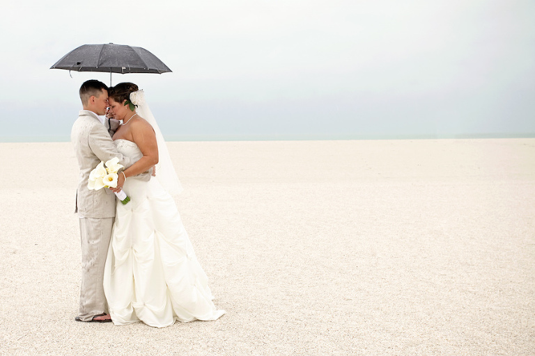 Outdoor Beach Wedding Portrait of Bride and Groom in the Rain with Umbrella | Andi Diamond Photography