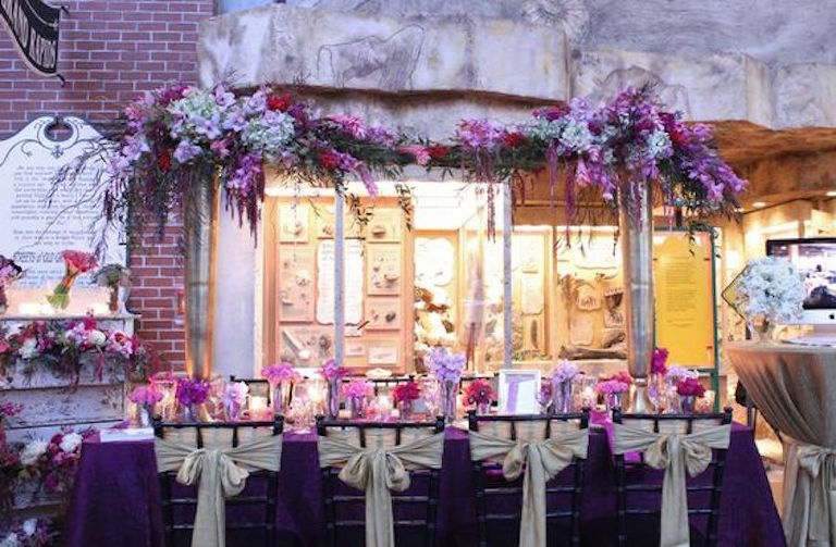 Dark Purple Wedding Table Linens with Extravagant Floral Arch and Gold Chair Sash Bows | Tampa Bay Wedding Rental Linens by Connie Duglin Specialty Linens