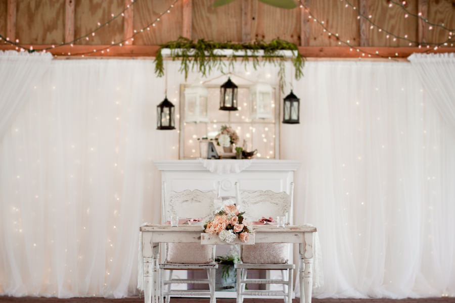 Vintage Wedding Reception Sweetheart Table Decor with Antique, White Wooden Table and Chairs, Hanging Lanterns, and Pink and Ivory Flowers at Barn Wedding Reception Sweetheart Table Decor with Antique, White Wooden Chairs and Pink Linens and Ribbon Table Runner | Rustic Tampa Bay Wedding Venue Cross Creek Ranch