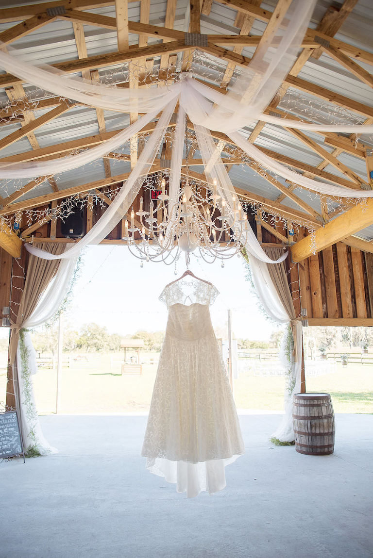 Ivory, Lace Wedding Dress Hung on Chandelier in Wooden Barn