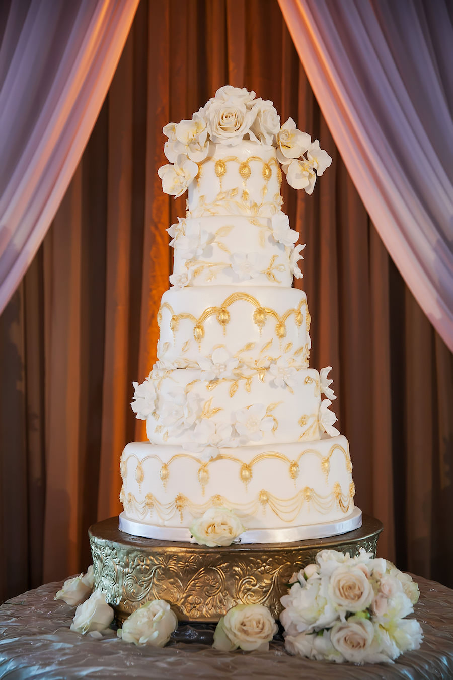 Five Tier Round Ivory and Gold Wedding Cake with Ivory Roses on Brass Cake Stand and Specialty Linen   St. Petersburg Wedding Linen Rentals by Over The Top Linens   St. Pete Wedding Photographer Limelight Photography