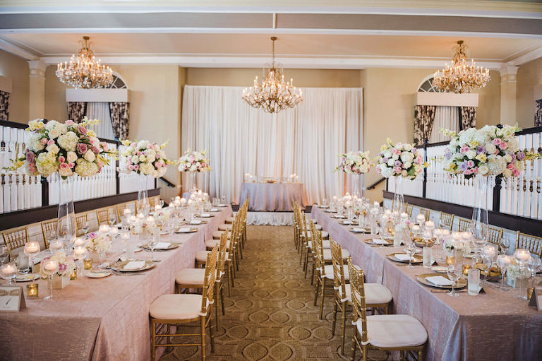 Long Feasting Tables with Candles and Tall Ivory, Pink and Purple Centerpieces on Lilac Specialty Linens with Gold Chiavari Chairs at Tampa Wedding Reception Venue Loews Don CeSar Hotel | Photography by Tampa Wedding Photographer Marc Edwards Photographs
