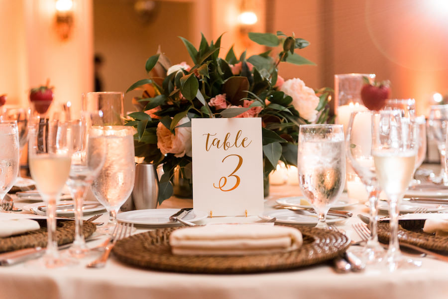 Wedding Reception Table Decor with Coral and Green Floral Centerpieces, Gold Foil Table Numbers, and Wicker Chargers
