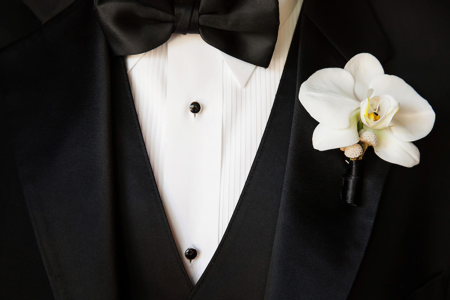 Black Tuxedo with Black Vest and Bowtie and Orchid Boutonniere   St. Pete Wedding Photographer Limelight Photography