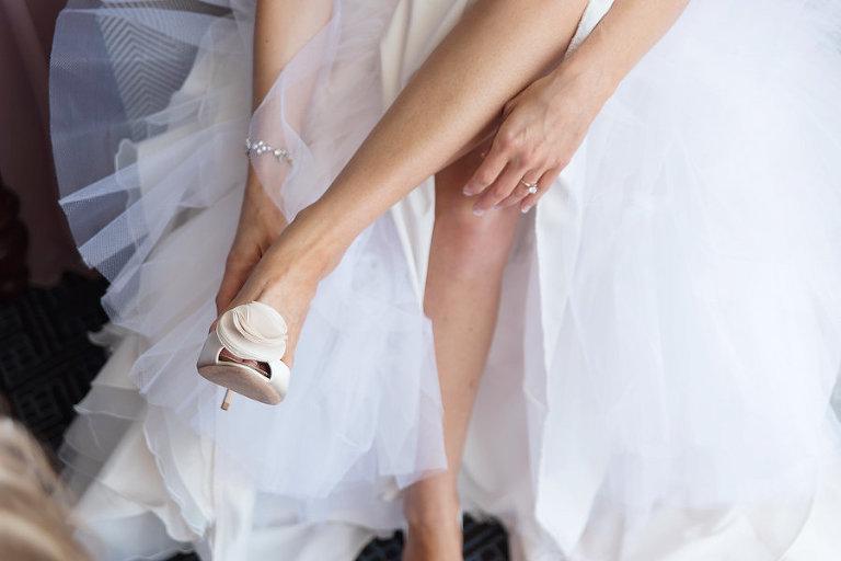 Bride Putting on Ivory, Badgley Mischka Wedding Shoes