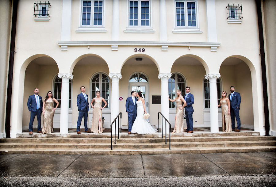 Outdoor, Bridal Party Wedding Portrait in Gold Sequined La Femme Bridesmaids Dresses and Blue Groomsmen Suits | Sarasota Wedding Venue Ca' d'Zan Mansion at The Ringling Museum