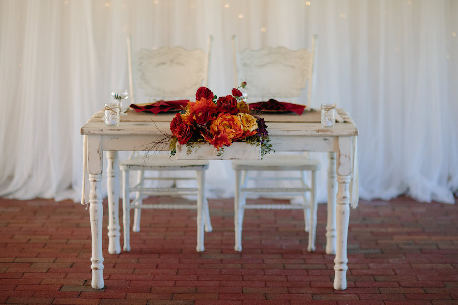 Dover Wedding Reception White, Antique Wooden Sweetheart Table with Purple, Red, and Yellow Fall Colored Floral Centerpiece