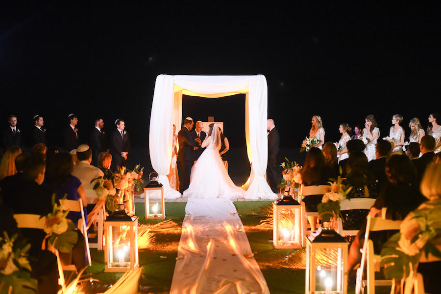 Nighttime Jewish Wedding Ceremony with Lantern Wedding Aisle Lighting and White Draped Chuppah | Clearwater Beach Lighting Nature Coast Entertainment Services