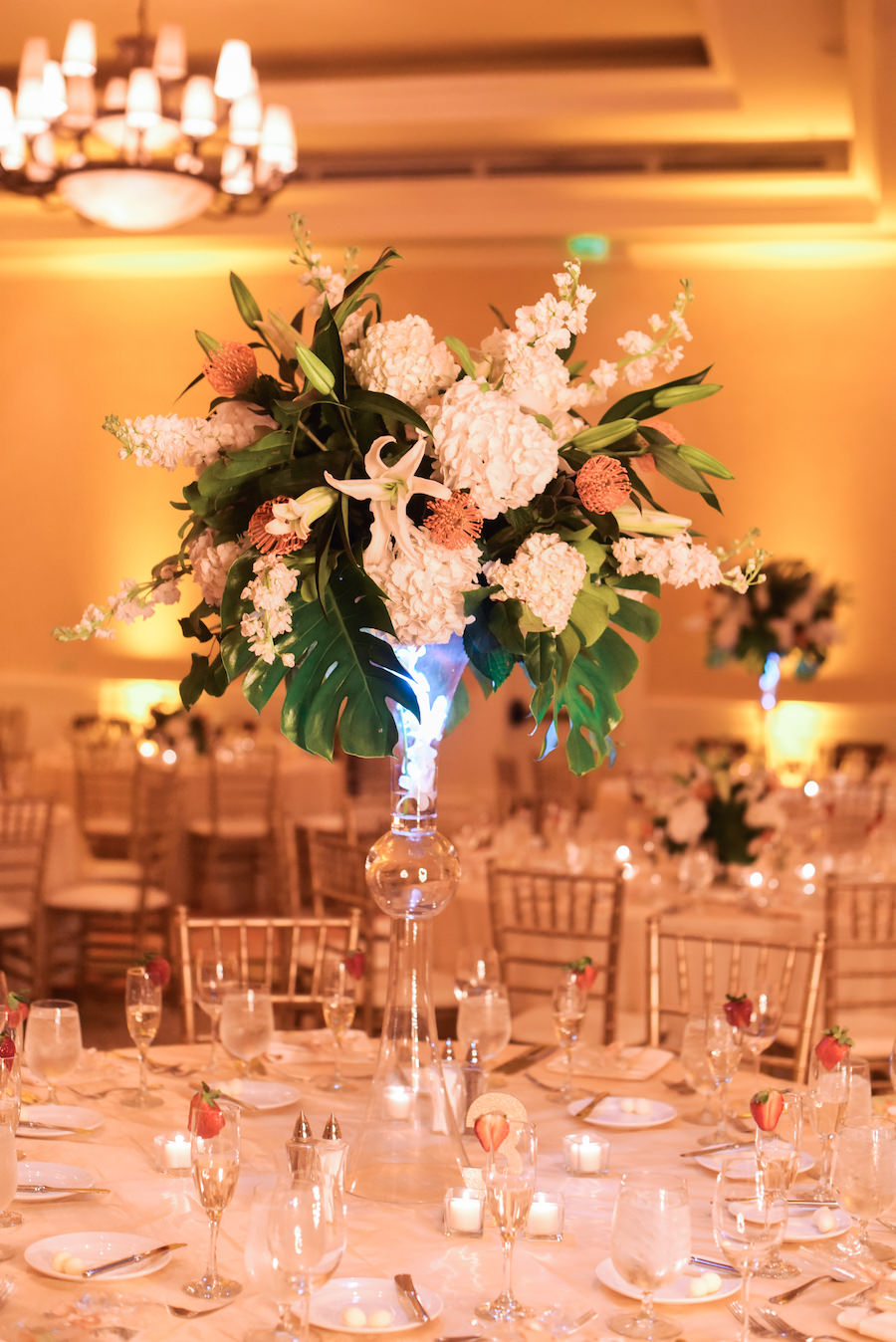 Formal, Beach Wedding Reception Décor with Gold, Ivory, Green and Coral Tall Centerpieces with Hydrangea and Tropical Greenery | Lighting by Nature Coast Entertainment Services