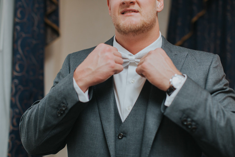 Groom Getting Dressed in Grey Suit and White Bowtie | Cleveland Browns Football Player Charley Hughlett Wedding