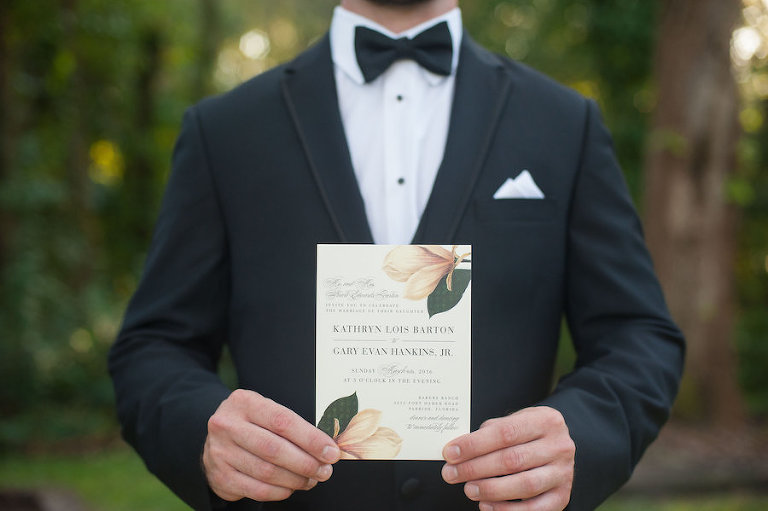 Groom in Black Tuxedo Holding Custom Ivory and Green Wedding Invitation With Magnolia Tree Floral Detail | Sarasota Wedding Stationery Citrus Press Co.