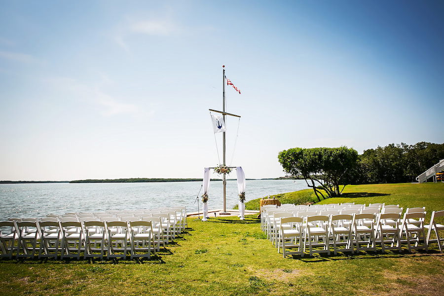 Waterfront St. Petersburg Wedding Ceremony with Draped Arch and Pastel Peach Flowers and White Folding Garden Chairs | St. Petersburg Wedding Venue Tampa Bay Watch