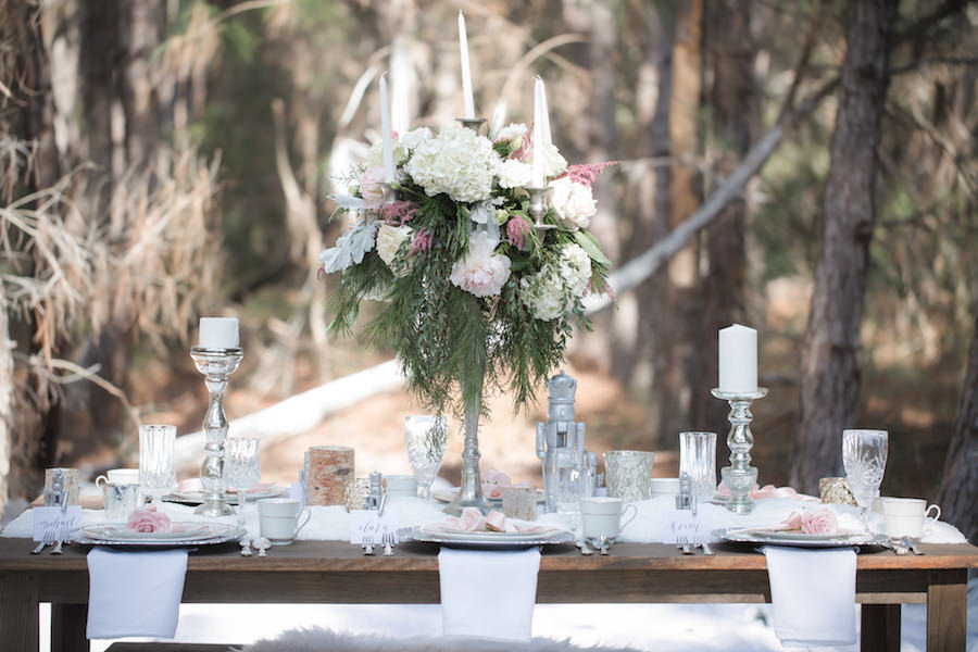Nutcracker Ballet Styled Wedding Shoot   Outdoor Winter Inspired Wedding Reception with Faux Fur and Wooden Farm Tables with Silver Charger Plates with Vintage China Dishes with Tall Ivory Blush and Pink Floral Centerpieces   Ever After Vintage Weddings Tampa Bay Wedding Rental Company and Event Stylist