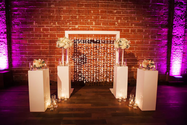 Paper Crane Backdrop and Ivory Floral Wedding Ceremony Altar Arrangements with Exposed Brick Wall | St. Petersburg Wedding Venue NOVA 535