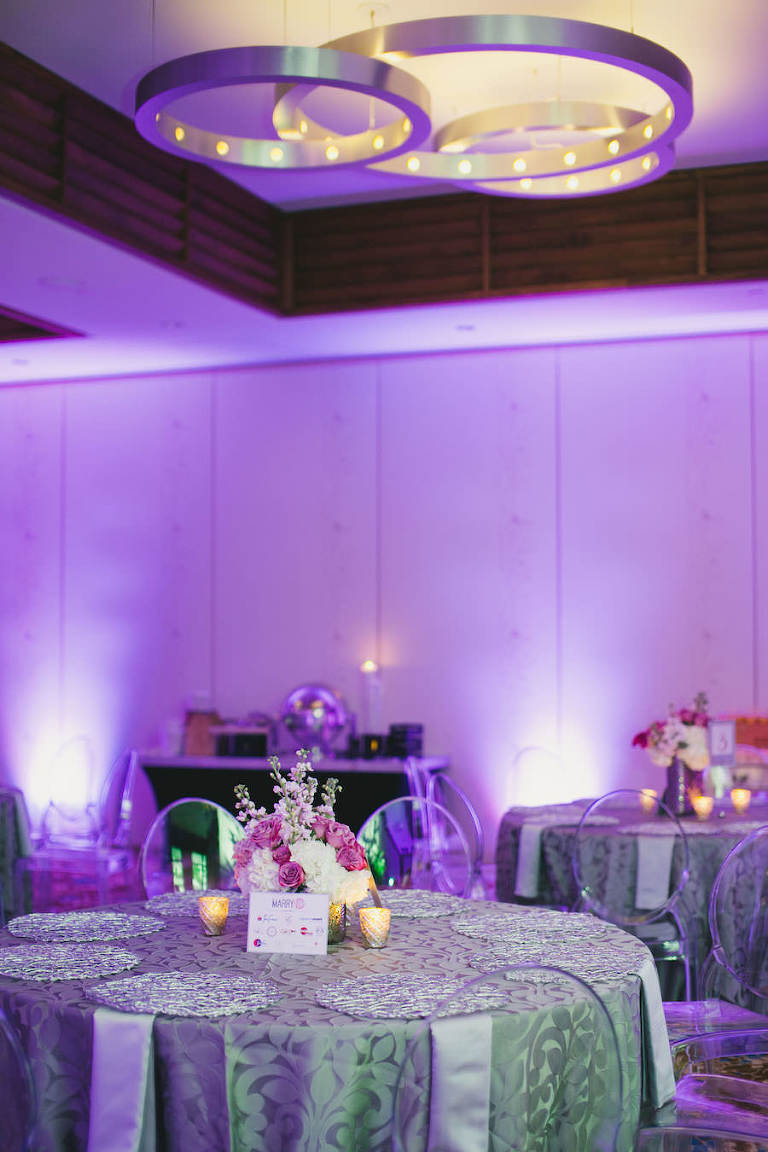 Silver Reception Decor with Pink and White Wedding Centerpieces, Purple Uplighting and Ghost Chairs | Linens by Over the Top Rental Linens | Chargers by Signature Event Rentals | Lighting by Gabro Event Services | Roohi Photography