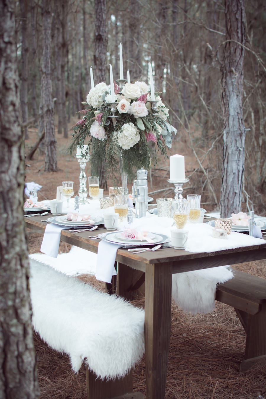 Outdoor Winter Inspired Wedding Reception with Faux Fur and Wooden Farm Tables with Tall Blush Pink and Ivory Floral Centerpieces | Ever After Vintage Weddings Tampa Bay Wedding Rental Company and Event Stylist
