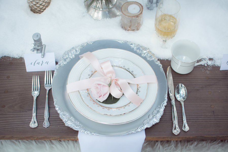 Outdoor Winter Inspired Wedding Reception with Faux Fur and Wooden Farm Tables with Silver Charger Plates with Vintage China Dishes | Ever After Vintage Weddings Tampa Bay Wedding Rental Company and Event Stylist