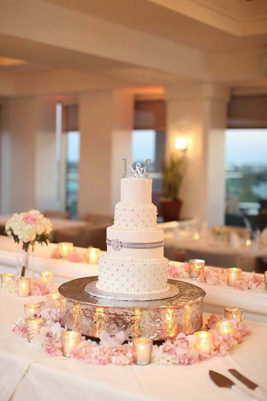 Four Tiered white Wedding Cake on Large Silver Cake Stand with Embellished Design | Tampa Wedding Cake Bakery A Piece of Cake and Desserts