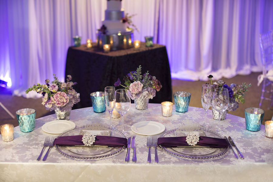 Beaded Glass Charger with Silver Wedding Menu and Purple Napkin with Rhinestone Holder | Purple and Deep Red Centerpieces with Candles on Ivory Linens | Sweetheart Table Wedding Reception Ideas & Inspiration | Special Moments Event Planning | Connie Duglin Linens
